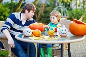 Adorable Kid Boy And His Father  Making Jack-o-lantern For Halloween In Autumn Garden