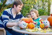 Cute Kid Boy And His Father  Making Jack-o-lantern For Halloween In Autumn Garden