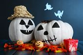 Halloween pumpkins and candles on wooden table on dark color background