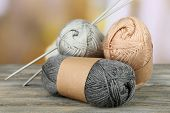 Knitting yarn with knitting needles on wooden table, on light background