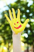Smiling colorful hand on natural background