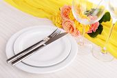 Table setting with yellow rose on plate