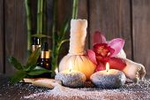 Spa set on bamboo mat on wooden wall background