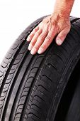 Man's hand holding tyre isolated on white