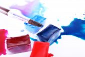 Watercolor paint cubes with brush and spilled paint isolated on white