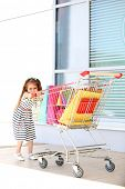 Happy little girl with shop bags in supermarket trolley, outdoors