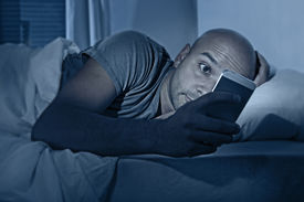 picture of addicted  - young cell phone addict man awake at night in bed using smartphone for chatting flirting and sending text message in internet addiction and mobile abuse concept - JPG