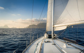 pic of sailing vessels  - Cruising sailiing yacht with hoisted sails going to rock island - JPG