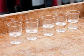 image of shot glasses  - Row of shot glasses with vodka on wooden board - JPG