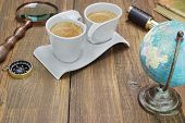 foto of spyglass  - Earth Globe Vintage Spyglass Magnifying Glass Compass Two Notebooks Smoking Pipe and Two Espresso Coffee Cups On The Grunge Wooden Table - JPG