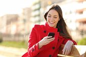 stock photo of bench  - Girl texting on the smart phone sitting in a park wearing a red jacket and sitting in a bench in a park - JPG