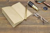 image of spyglass  - Open Vintage Notebook With Blank Pages Gold Fountain Pen Glasses Retro Magnifier Compass and Spyglass On Grunge Woodeen Table Background - JPG