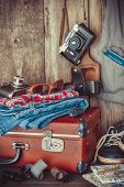 stock photo of old suitcase  - Old travel suitcase sneakers clothing sunglasses maps filmstrip and retro film camera  - JPG