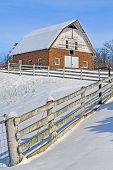 image of red barn  - An old red brick barn and a rugged white fence are covered in winter snow on a sunny day - JPG