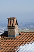 stock photo of red roof tile  - the old chimney on the roof of the house with red roof tiles - JPG