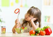 stock photo of little kids  - Cute kid girl not wanting to eat healthy food at kitchen - JPG
