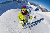 stock photo of caucus  - View of woman in mask standing and holding ski and ski poles during sunny winter day on Krasnaya polyana ski resort and Caucasus mountains in Sochi - JPG