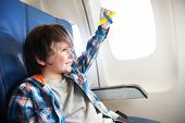 image of jet  - Little boy play with toy plane in the commercial jet airplane flying on vacation - JPG