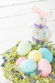 pic of hare  - Wicker nest with easter eggs and cute hare on white wooden background - JPG