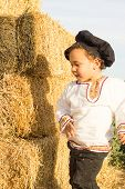 stock photo of haystack  - Country boy in national costume plays in a haystack.