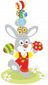 foto of juggling  - Little rabbit juggling with colorful Easter eggs - JPG