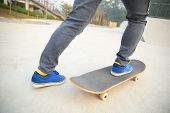 image of skateboarding  - young skateboarder legs skateboarding at skatepark ramp - JPG