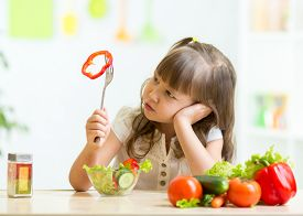 foto of dislike  - Cute kid girl not wanting to eat healthy food at kitchen - JPG