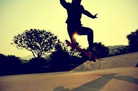 stock photo of skateboard  - young skateboarder skateboarding trick ollie at skatepark - JPG