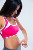 picture of skinny fat  - Sports woman touching her belly fat over gray background - JPG