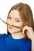 pic of moustache  - Happy teenage woman making moustache from hair - JPG