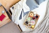 stock photo of bed breakfast  - High Angle View of Bathrobe and Breakfast Tray on Unmade Bed Beside Night Table with Red Book in Hotel Room - JPG