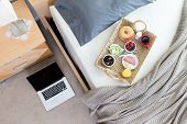 picture of bed breakfast  - High Angle View of Open Laptop on Floor Beside Unmade Bed in Hotel Room with Wicker Breakfast Tray - JPG