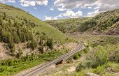 picture of bend  - Double set of railroad tracks crossing a river and rounding a bend on a spring day - JPG