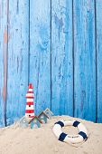 stock photo of lighthouse  - Beach with lighthouse and life buoy in front of vintage blue background - JPG