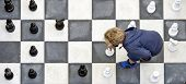 pic of chess pieces  - Young boy moving a white pawn during a chess game on an outdoor chess board - JPG