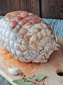 foto of bay leaf  - Raw chicken roll ready to roast on a cutting board with garlic and bay leaves - JPG