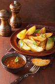 foto of baked potato  - baked potato wedges in plate over brown rustic table - JPG