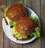 foto of whole-wheat  - Homemade Hamburgers with Roasted Beef LettuceTomato Onions Cheese and Bacon with Whole Wheat Bun on White Plate on Rustic Wooden background - JPG