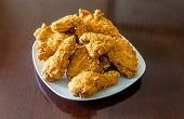 pic of southern fried chicken  - Fresh crispy fried chicken on a square white plate on a polished wood table - JPG