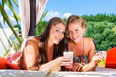 stock photo of sun-tanned  - Two woman lying in the sand on the beach - JPG