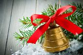 stock photo of christmas bells  - Christmas composition with golden bell with red satin ribbon bow and branch of christmas tree - JPG