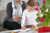 picture of homework  - girl sitting on sofa  and doing  at homework  with the help of grandmother - JPG