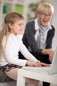 picture of grandma  - adorable little girl using laptop surprised grandma looking - JPG