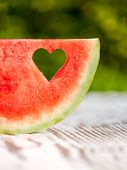 pic of watermelon slices  - slice watermelon with a hole in the shape of heart on a wooden table - JPG