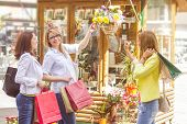 pic of flower shop  - Happy Shopping Female Friends with bags watching flowers in the street shop - JPG