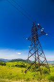 stock photo of power transmission lines  - High voltage electric power lines tower over the mountains - JPG