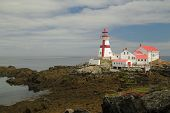 stock photo of puffy  - East Quoddy Head Light on Campobella Isand New Brunswick Canada at low tide on beautiful day soft puffy clouds in blue sky - JPG