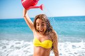 foto of emotional  - Emotional woman pouring water from watering can on the beach - JPG