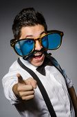 stock photo of moustache  - Young man with false moustache and large sunglasses isolated on gray - JPG