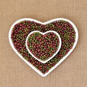 stock photo of mung beans  - Mung and aduki beans in a heart shaped bowl over hessian background - JPG
